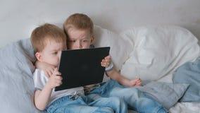 Kinder mit Tablette Zwei Jungenzwillingskleinkinder, die Karikatur der Tablette liegt auf dem Bett betrachten stock footage
