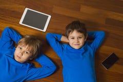 Kinder mit Tabletten-PC, Handy, der auf Bretterboden liegt Beschneidungspfad eingeschlossen Bildung, lernend, Technologiekonzept Lizenzfreie Stockbilder