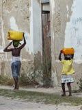 Kinder mit watercans auf Insel von Mosambik stockfoto
