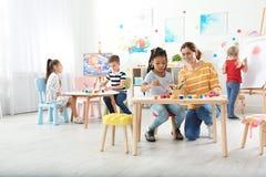 Kinder mit weiblichem Lehrer an malender Lektion stockfoto