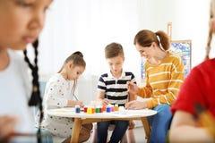 Kinder mit weiblichem Lehrer an malender Lektion lizenzfreies stockbild