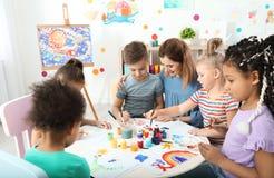 Kinder mit weiblichem Lehrer an malender Lektion lizenzfreie stockfotos