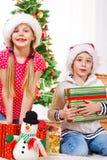 Kinder mit Weihnachtsgeschenken Lizenzfreie Stockfotos