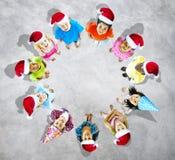 Kinder mit Weihnachtshüten im grauen Hintergrund Stockbilder