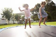 Kinder an Montessori-Schule, die Spaß auf Trampoline im Freien hat Lizenzfreie Stockfotografie