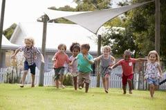 Kinder an Montessori-Schule, die Spaß draußen während des Bruches hat Stockbild