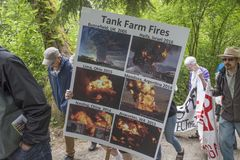 At the Kinder Morgan protest, protesters hold up a poster showing previous tank farm fires. Protesters against the Kinder Morgan pipeline expansion hold a sign stock photos