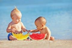 Kinder, nachdem Sie haben Sie Spaß und essen Sie Früchte auf Strand geschwommen sind Stockbild