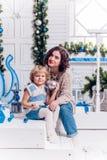 Kinder nahe bei einem Weihnachtsbaum geben sich Geschenke Stockfoto