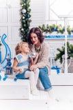 Kinder nahe bei einem Weihnachtsbaum geben sich Geschenke Stockbilder