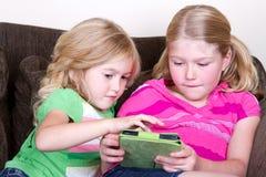 Kinder oder Schwestern, die Tablette verwenden Stockbilder