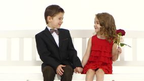 Kinder reiten ein Schwingen und ein kleiner Junge küsst das Mädchen auf der Backe Weißer Hintergrund stock footage