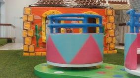Kinder ringsum das Karussell dreht sich in den Tummelplatz Aufstiege des kleinen Mädchens auf es stock video