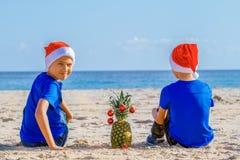 Kinder in roten Sankt-Hüten, die Spaß am Seestrand während der Weihnachtsferien haben stockbilder