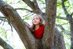 Kinder scherzen das Mädchen, welches das Klettern zu einem Baum in einem Park spielt lizenzfreies stockfoto