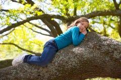 Kinder scherzen das stillstehende Lügen des Mädchens auf einem Baumast Lizenzfreie Stockfotografie
