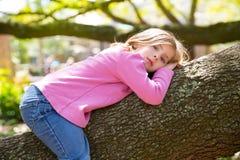 Kinder scherzen das stillstehende Lügen des Mädchens auf einem Baumast Lizenzfreies Stockbild