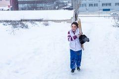Kinder schieben auf Schnee in der alte Schulart mit Hartholz Lizenzfreie Stockfotografie