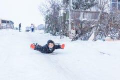 Kinder schieben auf Schnee in der alte Schulart mit Hartholz Lizenzfreies Stockfoto