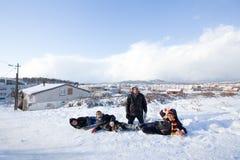 Kinder schieben auf Schnee in der alte Schulart mit Hartholz Lizenzfreie Stockfotos