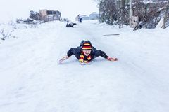 Kinder schieben auf Schnee in der alte Schulart mit Hartholz Lizenzfreie Stockbilder
