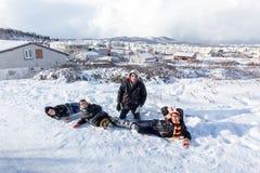 Kinder schieben auf Schnee in der alte Schulart mit Hartholz Stockfoto