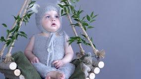 Kinder setzen, Baby mit großen Augen in der Miezekatze Zeit fest, die Kostüm auf dem hölzernen Schwingen sitzt, das mit grünen Ni stock video