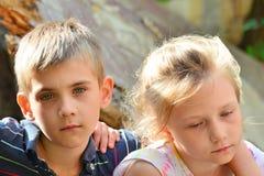 Kinder sind nahe dem ruinierten Haus, dem Konzept der Naturkatastrophe, Feuer und Verwüstung stockfoto