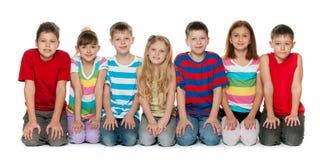 Kinder sitzen auf dem Boden Stockfotos
