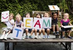 Kinder sitzen auf dem Holztisch, der ein Wortteam hält lizenzfreie stockbilder