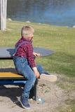 Kinder sitzen auf einer Holzbank im Freien stockfoto