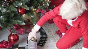 Kinder sitzen durch den Weihnachtsbaum stock video footage