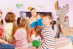Kinder sitzen um Lehrer und das Hören auf Geschichte Lizenzfreie Stockbilder
