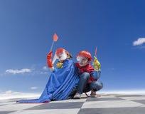 Kinder spielen die wunderbaren Helden unter klarem Himmel Lizenzfreies Stockfoto
