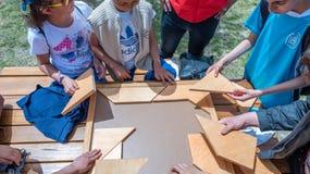 Kinder spielen ein traditionelles türkisches hölzernes Rätselspiel Stockbild