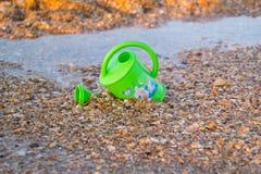 Kinder spielen für Bewässerungsblumen auf dem Strand Stockfotos