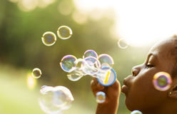 Kinder spielt Blasen in einem Park Lizenzfreie Stockfotos