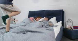 Kinder springen auf die Eltern, die zusammen im Bett am Morgen, glückliches Lächeln der Familie im berdoom liegen stock footage