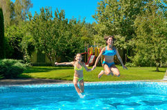 Kinder springen zum Swimmingpoolwasser und haben Spaß, Kinder auf Familienurlaub Lizenzfreie Stockfotos