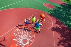 Kinder stehen auf dem Boden und Ball, die zum Korb fliegen Stockfoto
