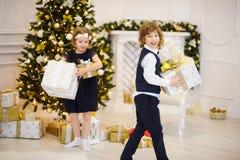 Kinder stehen nahe verziertem Weihnachtsbaum mit Kästen in den Händen Stockfoto