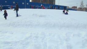 Kinder streben einen Antrieb von einem Hügel im Winter an stock footage
