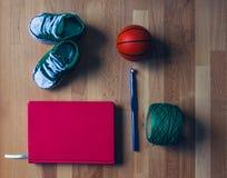 Kinder strickten Schuh mit rotem Buch, Ball, Häkelarbeit und Ball der Wolle lizenzfreies stockbild