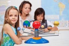 Kinder studieren das Sonnensystem unter ihrer Lehrerüberwachung Lizenzfreie Stockfotografie