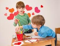 Kinder teilgenommen an Valentinstag-Künsten mit Herzen Lizenzfreie Stockfotografie
