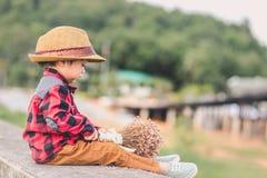 Kinder tragen Hut und Griffblume in den Parks stockbild