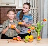 Kinder trinken zusammengedrückten Orangensaft von g Stockbilder