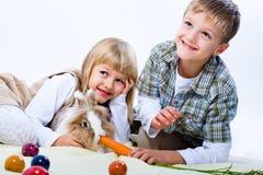 Kinder und östliches Kaninchen Stockfotografie