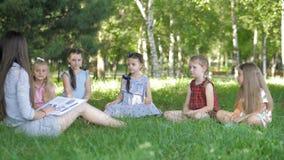 Kinder und Ausbildung, junge Frau bei der Arbeit als Erzieherlesebuch zu den Jungen und Mädchen im Park stock video