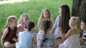 Kinder und Ausbildung, junge Frau bei der Arbeit als Erzieherlesebuch zu den Jungen und Mädchen im Park stock video footage